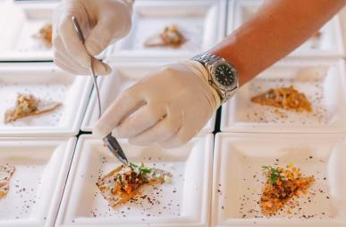 Picture of gloved hand putting the finishing touch on appetizers with a spoon.